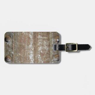 Placa de metal oxidada con los tornillos etiqueta para maleta