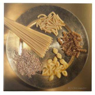 Placa de oro con las pastas y los granos del trigo azulejos cerámicos