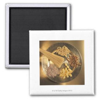Placa de oro con las pastas y los granos del trigo imán cuadrado