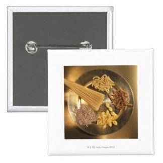 Placa de oro con las pastas y los granos del trigo pin cuadrado