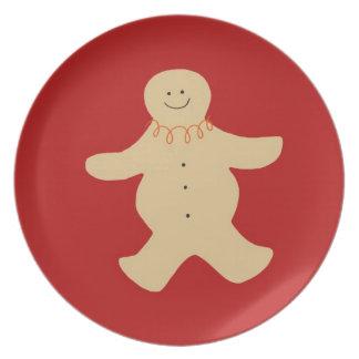 Placa del hombre de pan de jengibre en rojo plato de cena