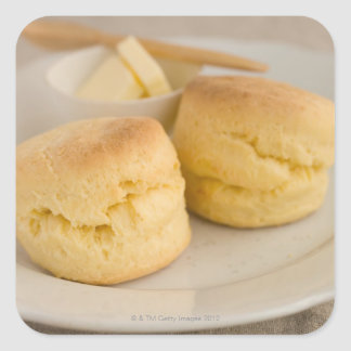 Plain scone with butter on plate square sticker