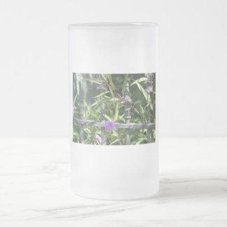 Planche la cerca, hojas del verde, flor púrpura jarra de cerveza esmerilada