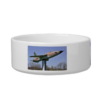 Plane in show with trees and sky in background pet bowls
