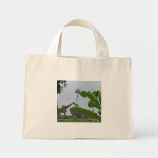 Plant and blue sky with giraffes in the background mini tote bag