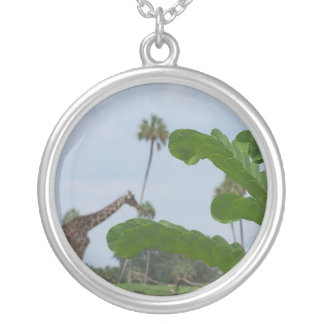 Plant and blue sky with giraffes in the background necklace