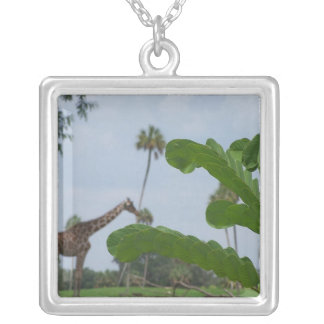 Plant and blue sky with giraffes in the background square pendant necklace
