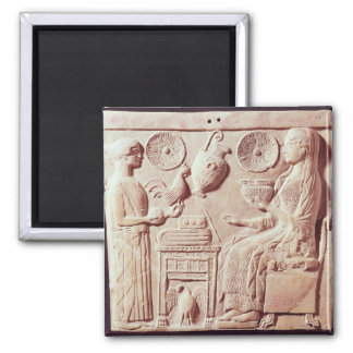 Plaque of a woman offering gifts to a seated magnet