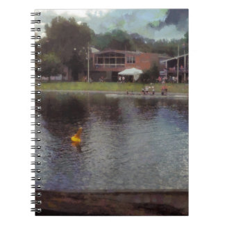 Plastic buoy in front of a lake spiral note book