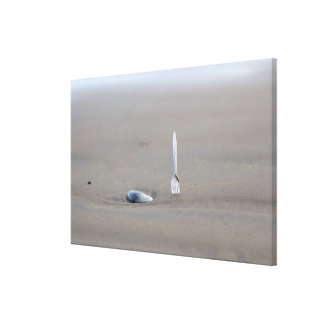 plastic fork sticking in sandy beach beside canvas prints