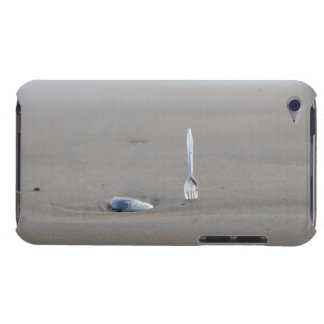 plastic fork sticking in sandy beach beside iPod touch cases