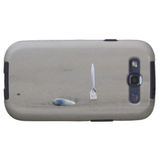 plastic fork sticking in sandy beach beside samsung galaxy SIII cover