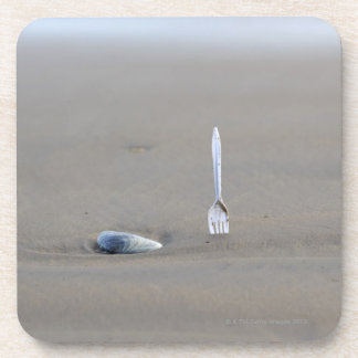 plastic fork sticking in sandy beach beside beverage coasters