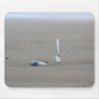plastic fork sticking in sandy beach beside mouse pads