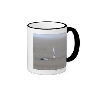 plastic fork sticking in sandy beach beside ringer coffee mug