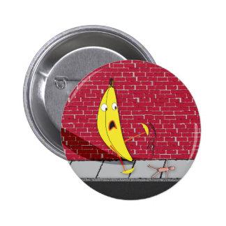 Plátano que se desliza en un botón de la persona pin
