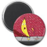 Plátano que se desliza en un imán de la persona