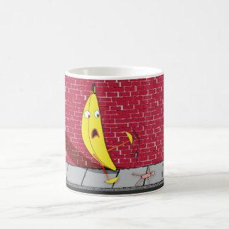 Plátano que se desliza en una taza de la persona