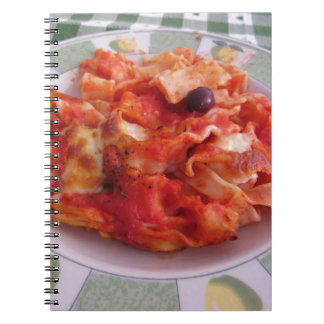 Plate of home made baked pasta on white background notebook