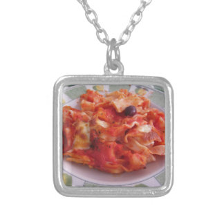 Plate of home made baked pasta on white background silver plated necklace