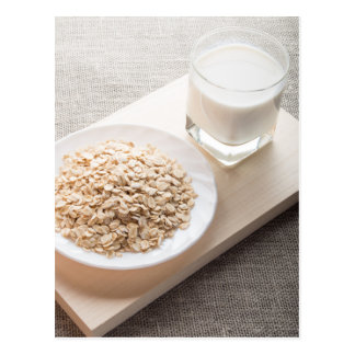 Plate with dry cereal and a glass of milk postcard