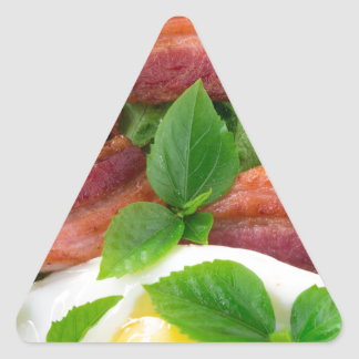 Plate with egg yolk, fried bacon and herbs triangle sticker