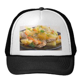 Plato de patatas guisadas con el pollo y las gorras
