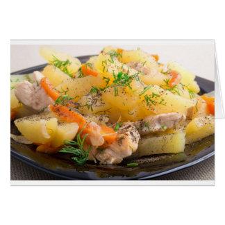 Plato de patatas guisadas con el pollo y las tarjeta de felicitación