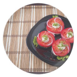 Plato negro con los tomates y la lechuga cortados