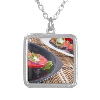 Platos vegetales de la berenjena guisada y del collar plateado