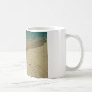 Playa arenosa tropical con huellas taza
