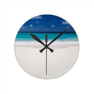 Playa blanca y cielo azul relojes
