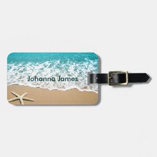 Playa con las estrellas de mar en la arena etiquetas maleta