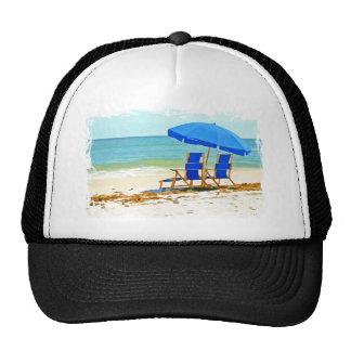 Playa, paraguas y sillas en la orilla gorras