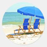 Playa, paraguas y sillas en la orilla etiqueta redonda