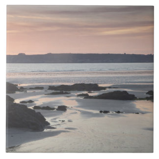 Playa rocosa en la puesta del sol azulejo cerámica