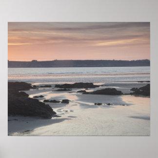 Playa rocosa en la puesta del sol póster