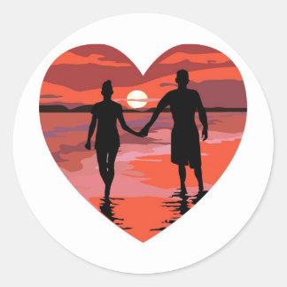 Playa roja de la puesta del sol del corazón que pegatina redonda