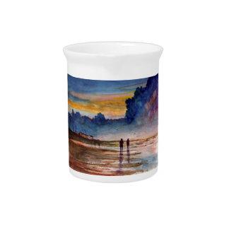 Playa tempestuosa de la puesta del sol que peina jarras