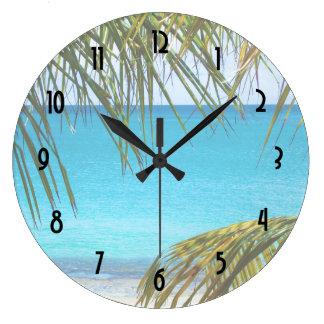 Playa tropical enmarcada con las frondas de la reloj redondo grande