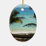 Playa tropical sombreada por las palmas adorno navideño ovalado de cerámica
