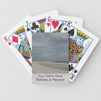 Playa y duna y embarcadero vacíos excepto una baraja cartas de poker
