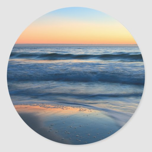 playa y ondas en la puesta del sol pegatina redonda
