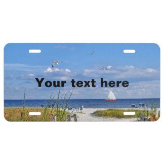 Playa y vista al mar con el velero placa de matrícula