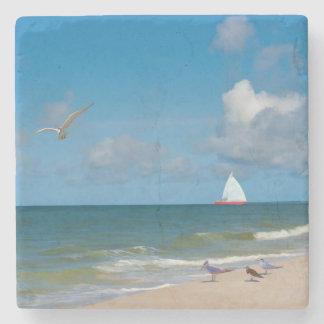 Playa y vista al mar con el velero posavasos de piedra