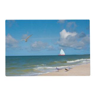 Playa y vista al mar con el velero tapete individual