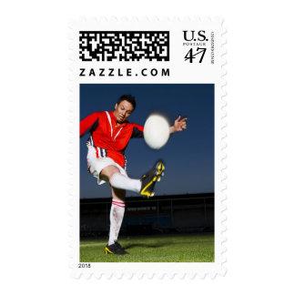 Player kicking ball postage stamp