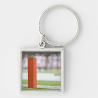 Players in background. Silver-Colored square keychain