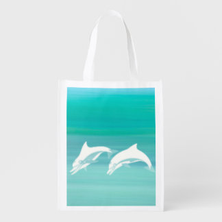 Playful dolphins in aquamarine ocean grocery bag
