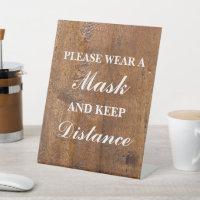Please wear a mask wood background pedestal sign